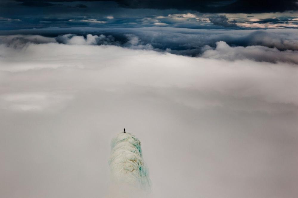 Альпинист стоит на вершине горы в Исландии.