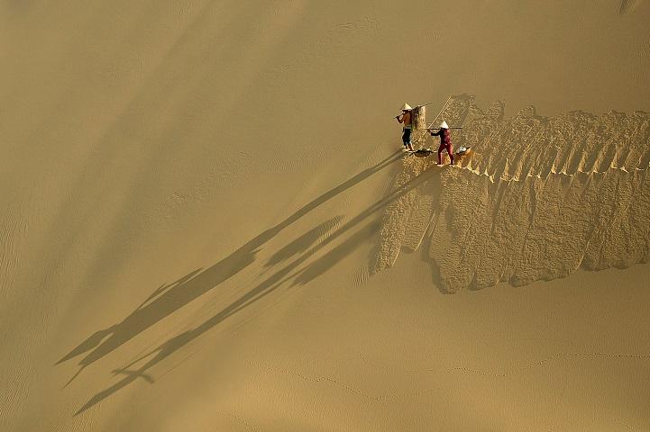 4. Победитель в регионе Восточная Азия и Тихоокеанский регион — «Преодоление бархана» (автор: Ле Минг Куок, Вьетнам). Рабочие утром переходят через дюны.