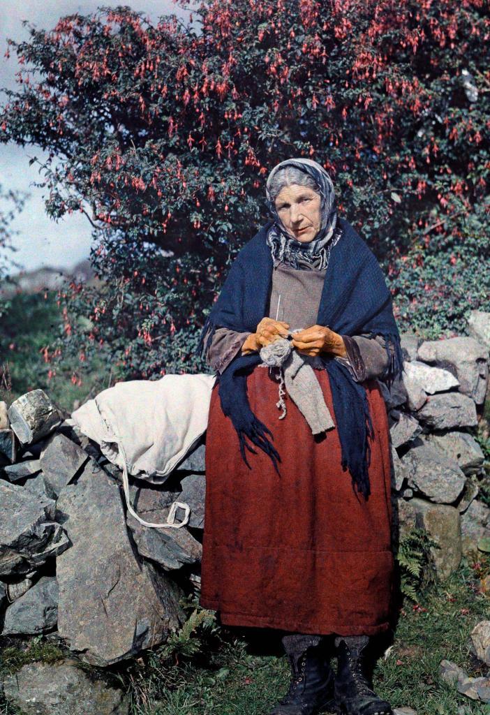 Женщина вяжет шерстяную одежду под фуксиевым деревом.