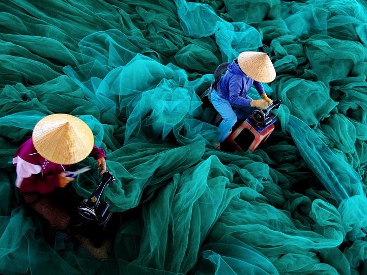 6. Поощрительная премия — «Для следующего путешествия» (автор: Лок Май, Вьетнам). В рыбацкой деревне Нха Транг, Вьетнам, женщины латают сети своих мужей, готовя их к следующему выходу в море.