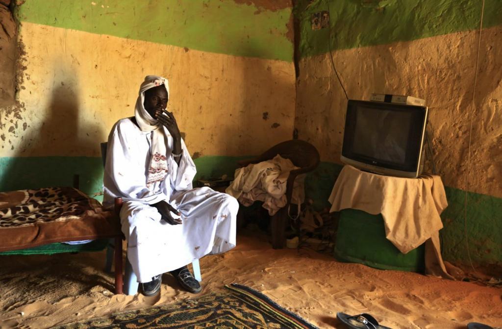 Член этнической группы бедуинов сидит перед своим телевизором в штате Северный Дарфур в Судане.