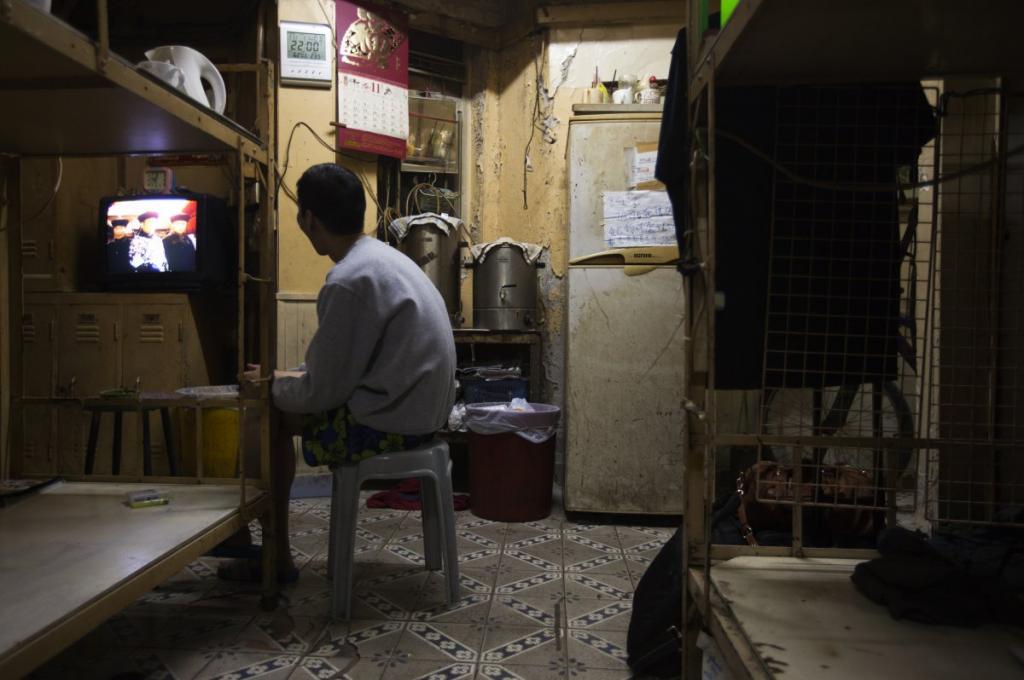 Житель Гонконга смотрит телевизор в тускло освещённом доме, который он арендует за 167 долларов в месяц.
