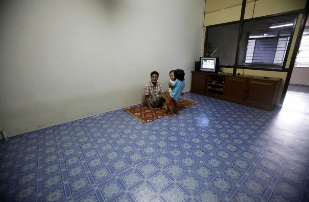 Семья беженцев из Мьянмы сидит на полу в пустой квартире в Куала-Лумпуре, столице Малайзии.