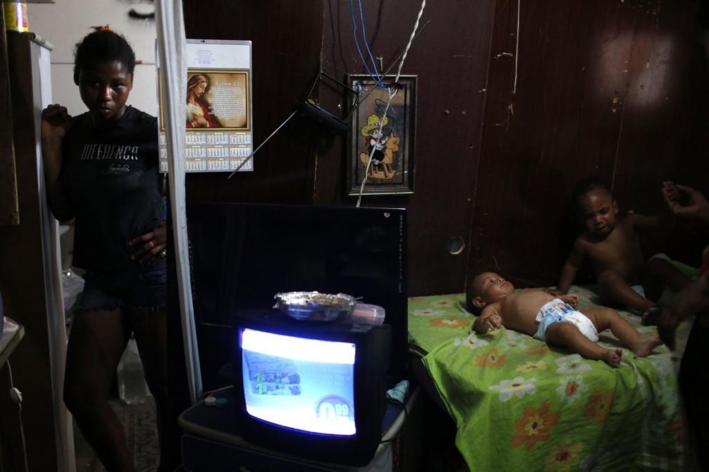 Приходящая няня стоит у входа в дом в трущобах Рио-де-Жанейро.