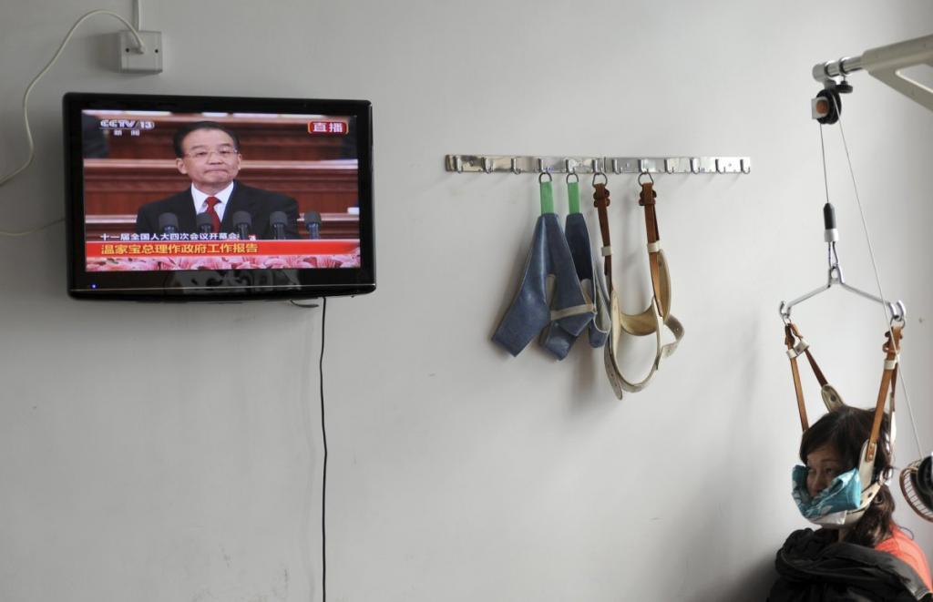 Пациентка смотрит по телевидению выступление правительства, находясь на лечении в госпитале округа Цзясин, Китай.