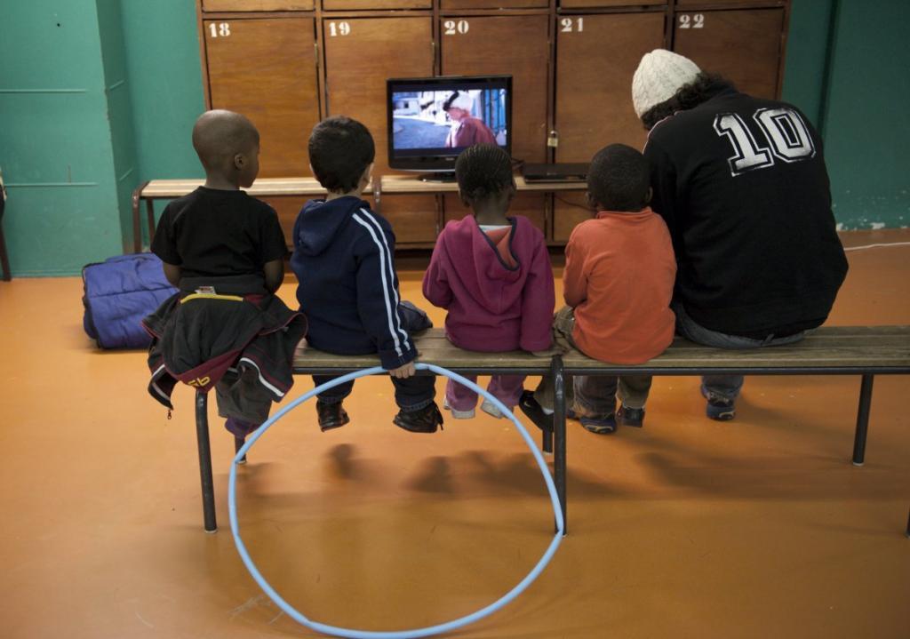 Дети сидят на скамейке и смотрят телепередачу в зале для занятий Сен-Мерри в Париже.