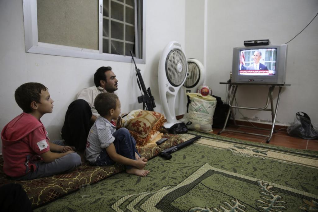Боец из Свободной сирийской армии в Гуте, Сирия, смотрит выступление Барака Обамы.