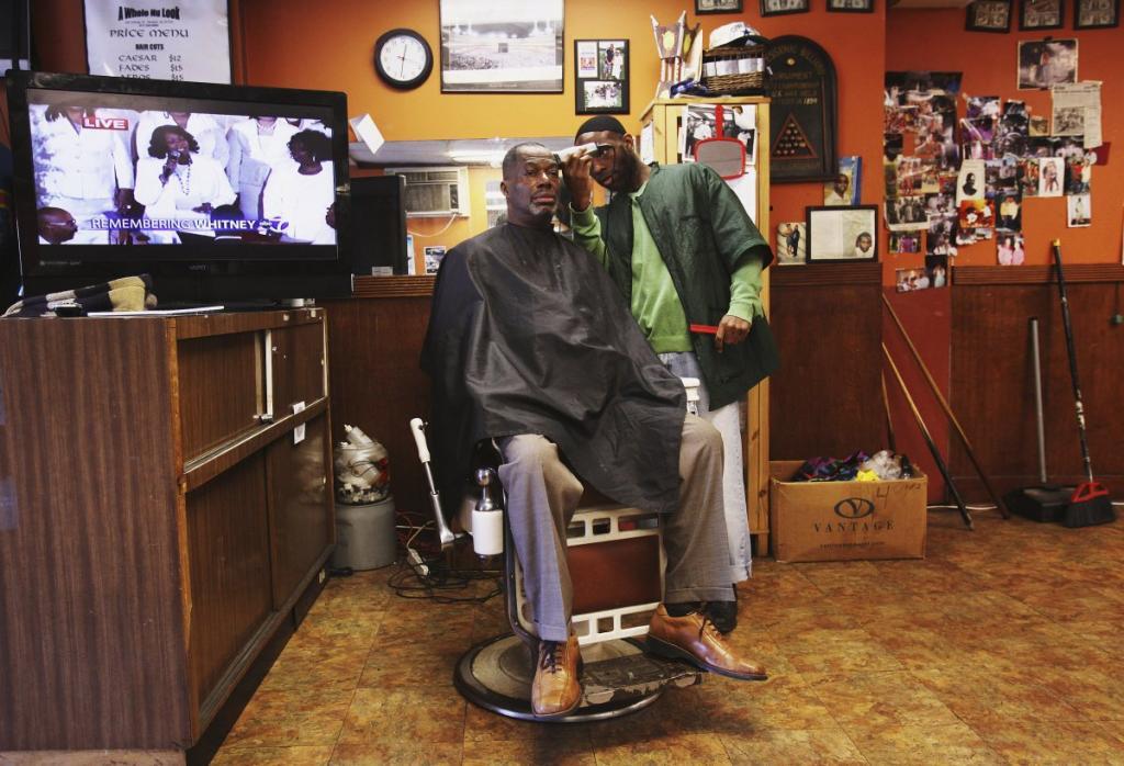 Мужчина стрижётся в Ньюарке, штат Нью-Джерси. В фоновом режиме работает телевизор.