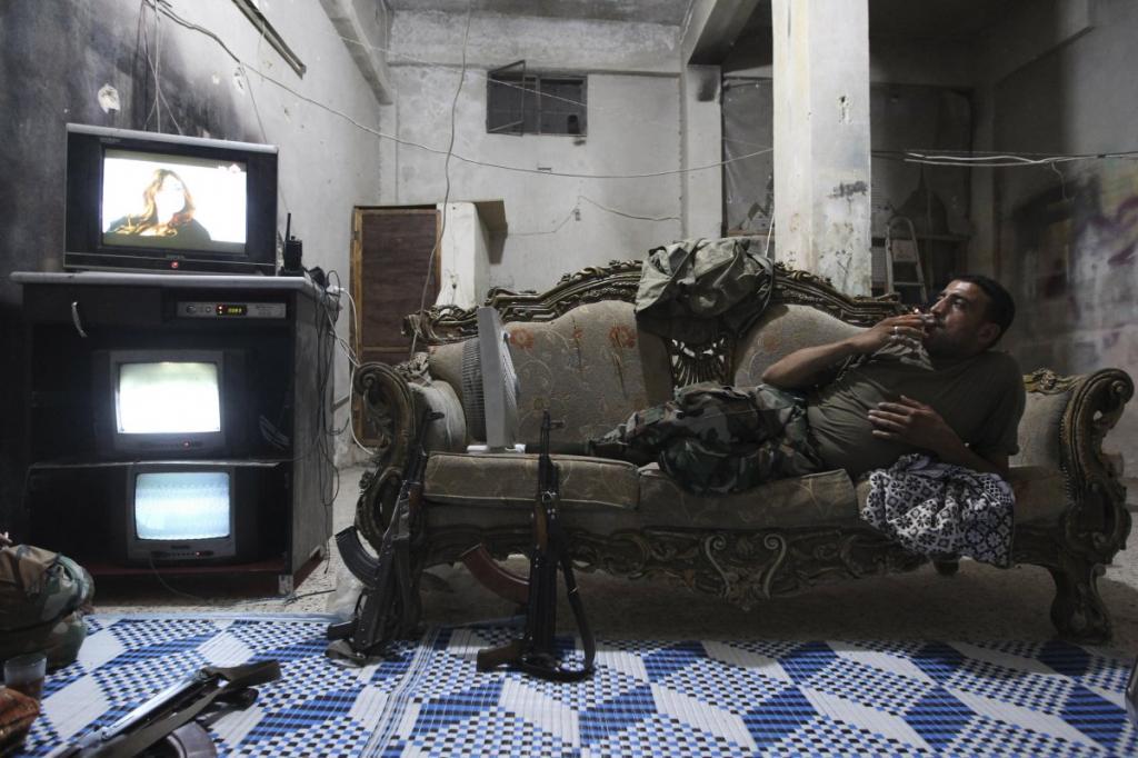 Боец Сирийской свободной армии смотрит телевизор в районе Алеппо Карм Аль-Джабаль.