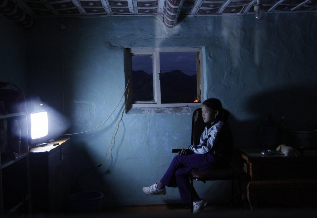 Девочка смотрит телевизор в провинции Булган, Монголия.