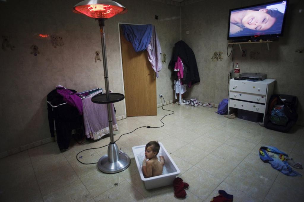 Мальчик принимает ванну при включенном телевизоре в доме дедушки и бабушки в районе Мадрида Пуэрта де Йерро.