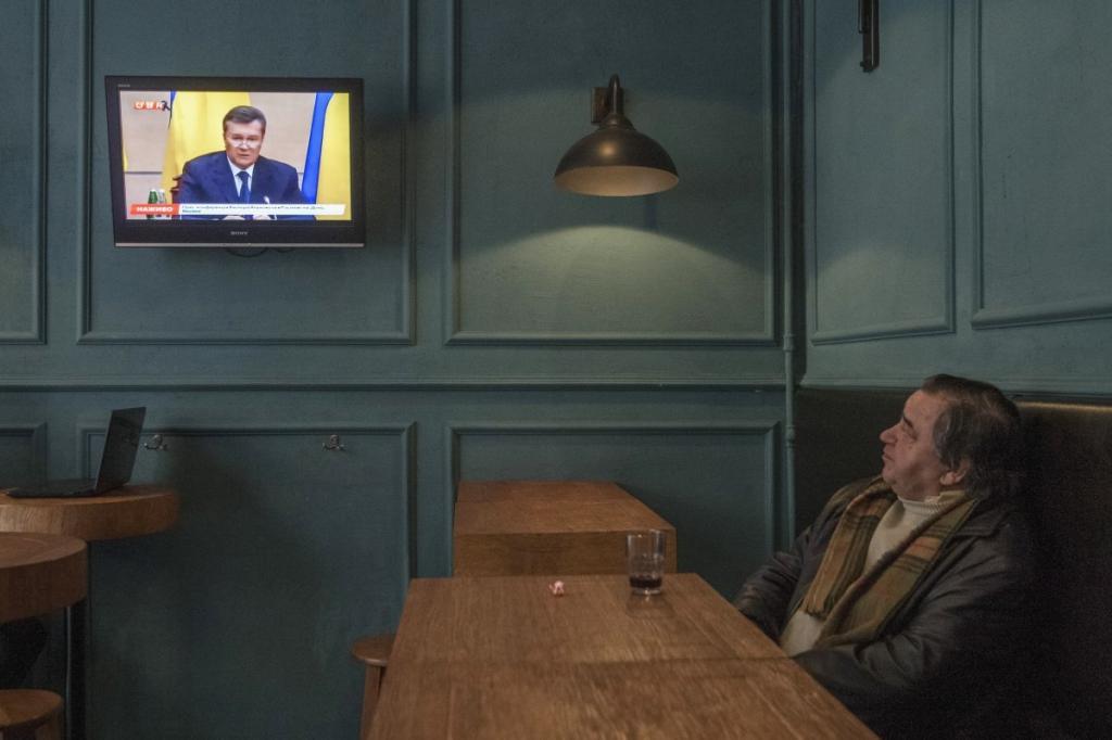 Киевлянин смотрит выпуск новостей и выпивает.