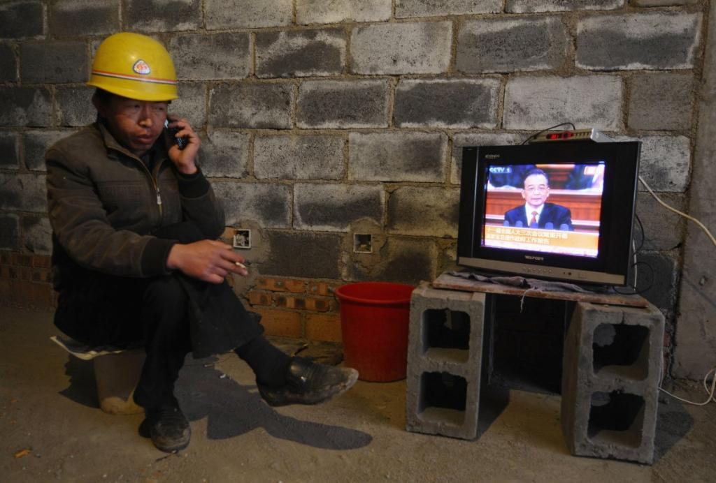 Рабочий в китайском городе Чанчжи говорит по телефону, курит сигарету и смотрит выступление правительства по телевизору.