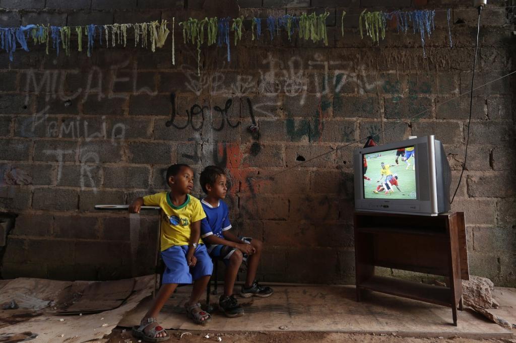 Во время чемпионата мира по футболу мальчишки на окраине города Бразилиа смотрят, как бразильская команда играет против Мексики.