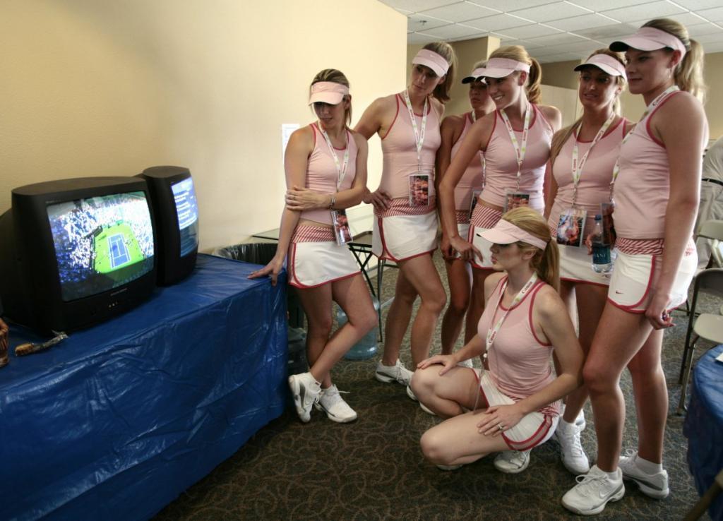 Модели, одетые как звезда теннисного корта Мария Шарапова, следят за её игрой по телевизору в Калифорнии.