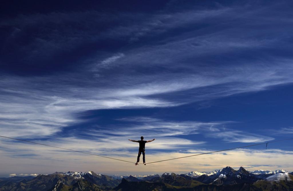 Слэклайнер на соревнованиях Highline Extreme Event проходит по тонкому тросу высоко над горами Швейцарии