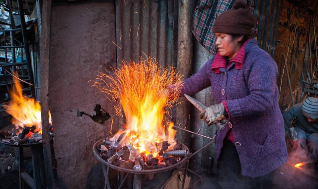 Женщин в шахты не допускают. Вместо этого, они выполняют роль подсобных рабочих. Эта, к примеру, изготавливает металлические крепежи для потолка рудника.