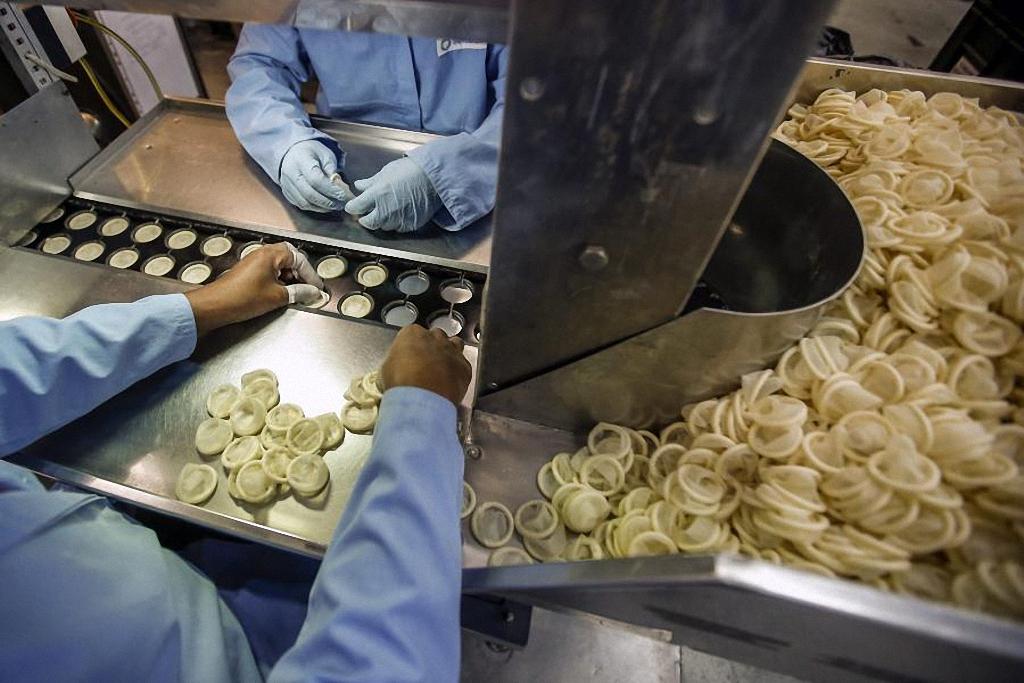 Работники фабрики в Порт-Кланге используют специальные формы перед упаковкой презервативов.