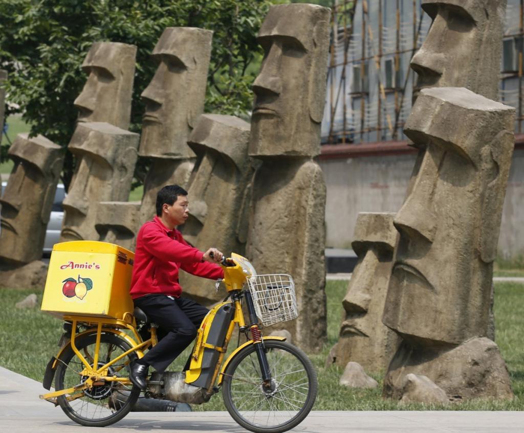 Реплики статуй Моаи (остров Пасхи, Чили) вдоль пешеходной дорожки в деловом районе Пекина.