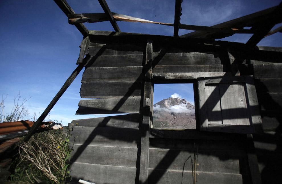Активный вулкан виден через окно заброшенного дома. Село Sibintun, Индонезия, 12 ноября 2015. (Фото Binsar Bakkara):