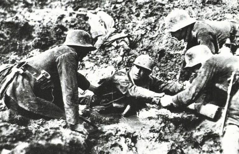 Немцы пытаются вытащить французского солдата из трясины, 1918.