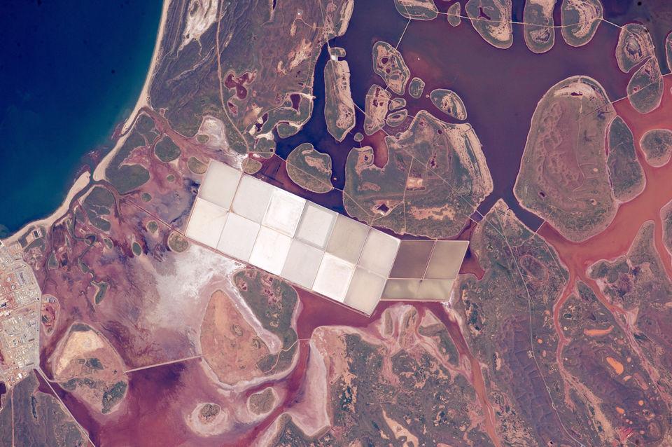 Соляные пруды на фоне мутной красно-коричневой дождевой воды в Западной Австралии