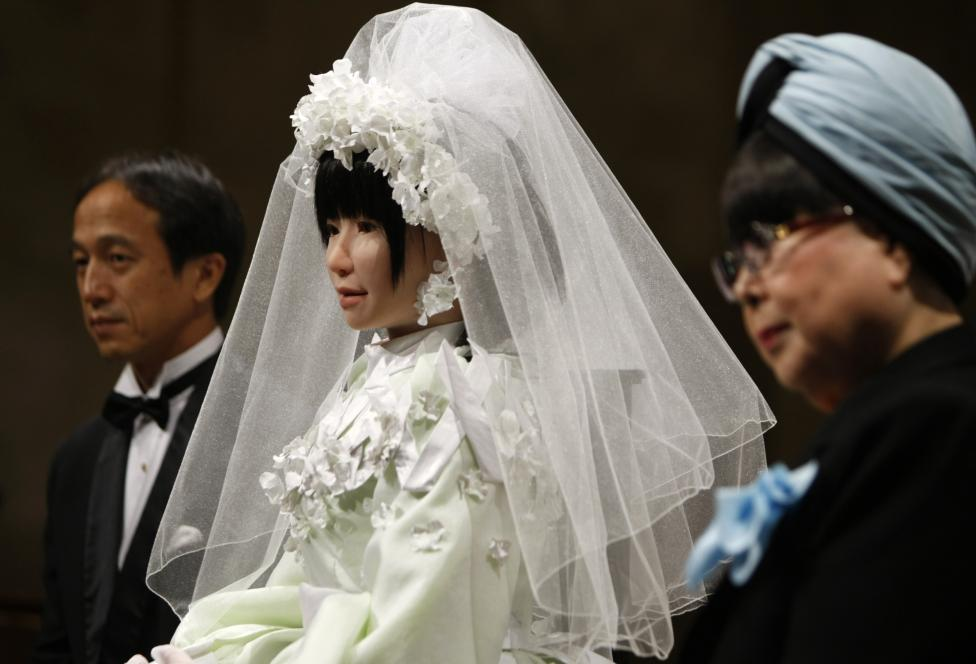 "HRP-4C humanoid robot ""Miim"" wearing a wedding dress by Japanese designer Yumi Katsura, attends a news conference with developer Yokoi after the 2009 Yumi Katsura Paris Grand Collection in Osaka"