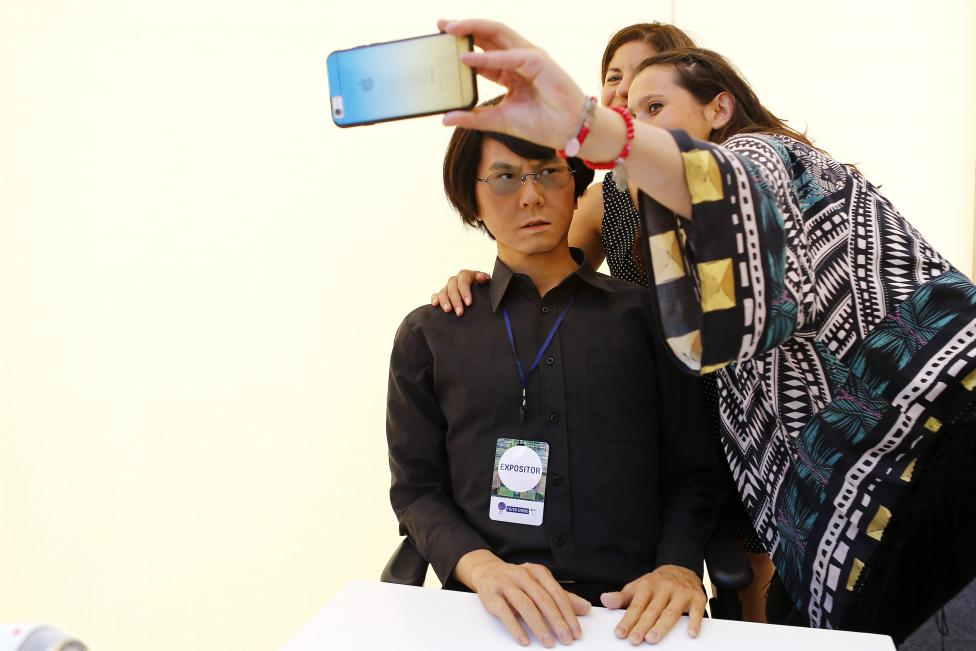 A visitor takes a selfie beside a Geminoid HI-2 robot, which is made in likeness of its creator, Japanese professor Ishiguro, during the opening ceremony of the Congress of the Future event in Santiago