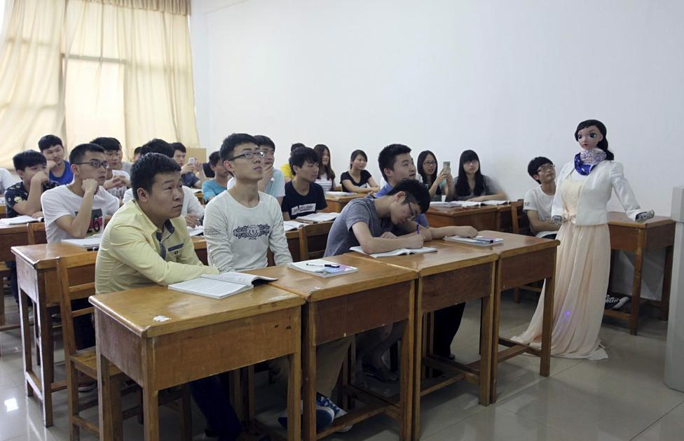 """A robot teacher named """"Xiaomei"""" (R) gestures during a demonstration at a class of Jiujiang University, in Jiujiang"""