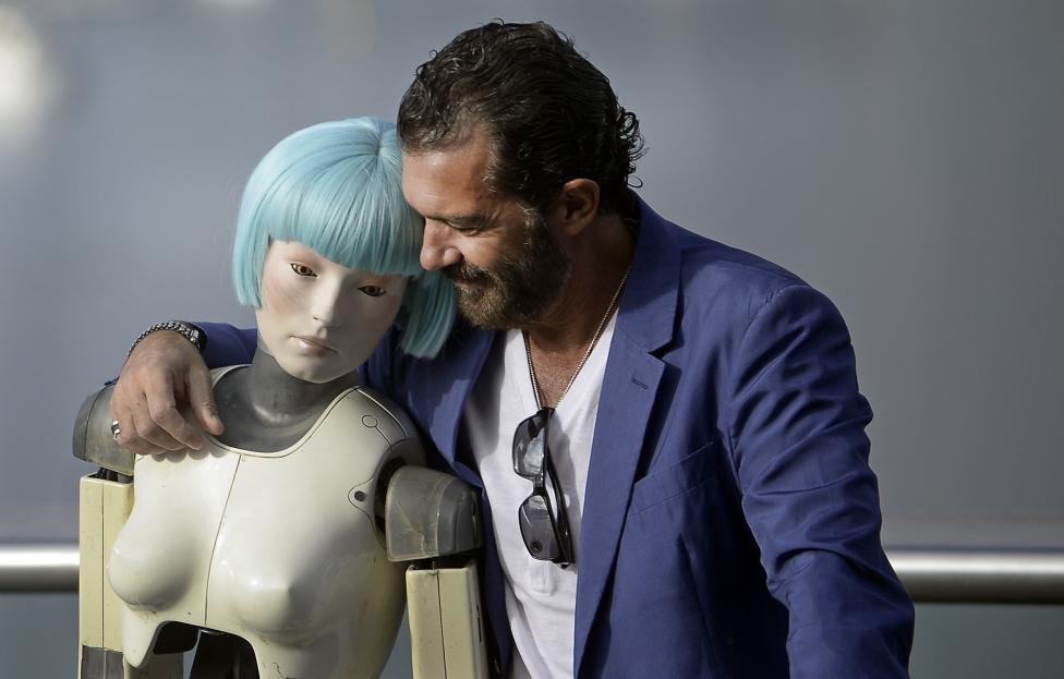 Spanish actor Banderas embraces a robot used in the film Automata during a photocall at the San Sebastian Film Festival