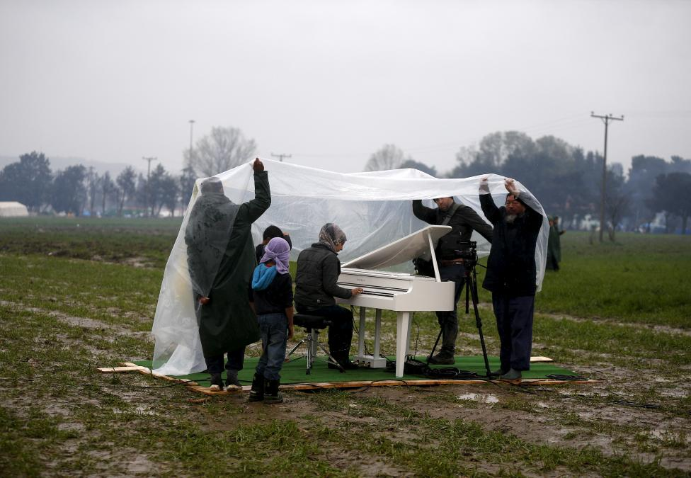 Chinese dissident artist Ai holds a rain cover to protect a Syrian refugee woman from the rain, as she performs in a field, on a piano brought by the artist, near a makeshift camp on the Greek-Macedonian border, near the village of Idomeni