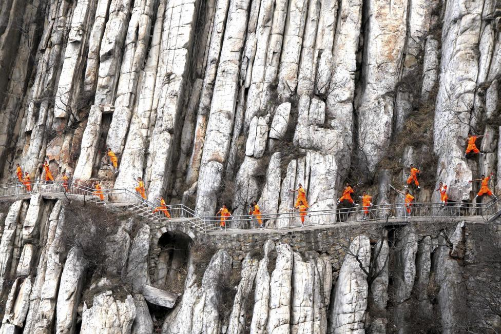 Students from a martial arts school practice Shaolin Kung Fu on cliffs in Dengfeng