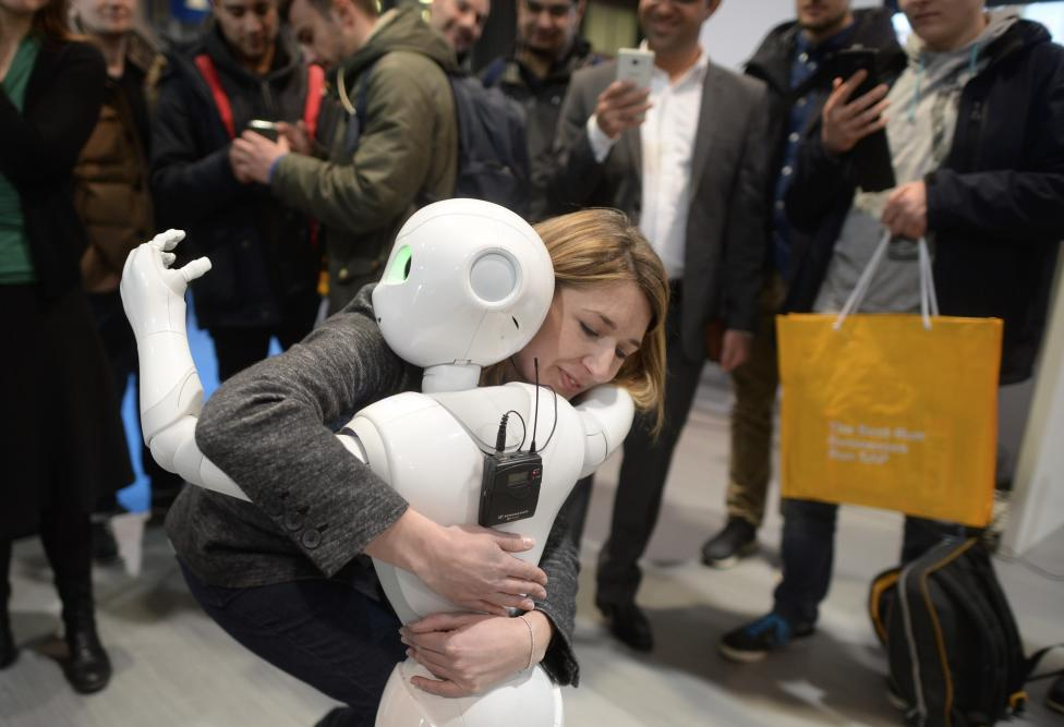 A woman embraces humanoid robot Pepper at the world's biggest computer and software fair CeBit in Hanover