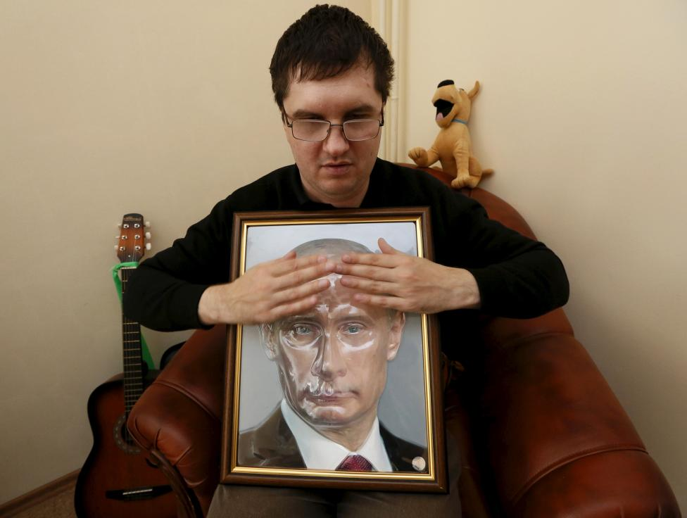 Visitor Roman Zorin touches a 3D portrait of Russia's President Vladimir Putin at a specialized library for blind and partially sighted people in Krasnoyarsk, Siberia