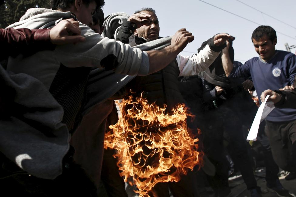 A refugee sets himself on fire during a protest by refugees and migrants demanding that the Greek-Macedonian border be opened, at a makeshift camp near the village of Idomeni, Greece,
