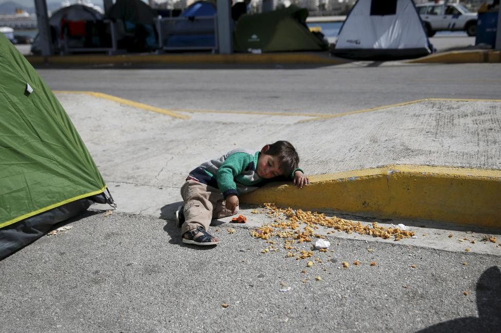 A boy plays with his toy truck at a makeshift camp for refugees and migrants at the port of Piraeus, near Athens