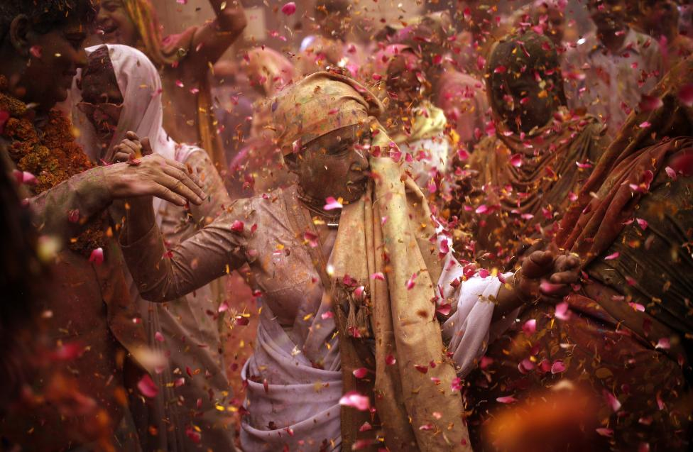 Widows daubed in colours dance as they take part in the Holi celebrations organised by non-governmental organisation Sulabh International at a temple at Vrindavan