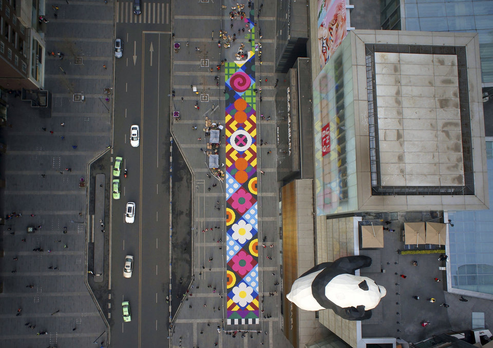 "Giant ""carpet"" with candies on a pedestrian street next to a panda sculpture hanging on the exterior wall of a department store, in Chengdu"