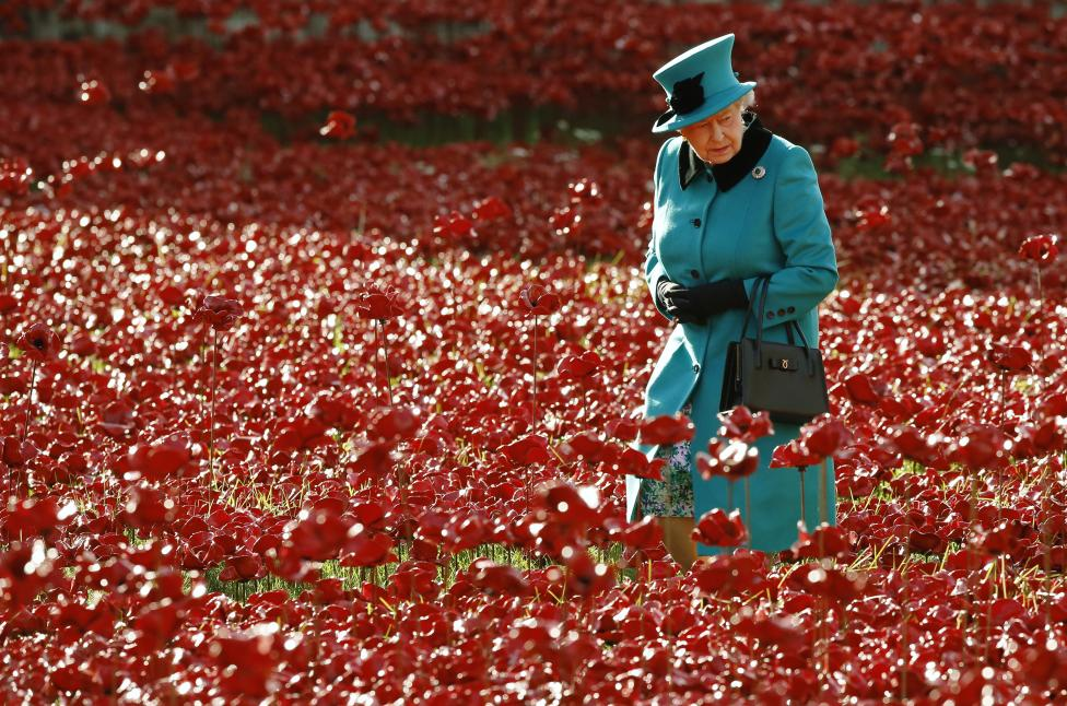 "Britain's Queen Elizabeth walks through a field of ceramic poppies that form part of the art installation ""Blood Swept Lands and Seas of Red"" at the Tower of London"