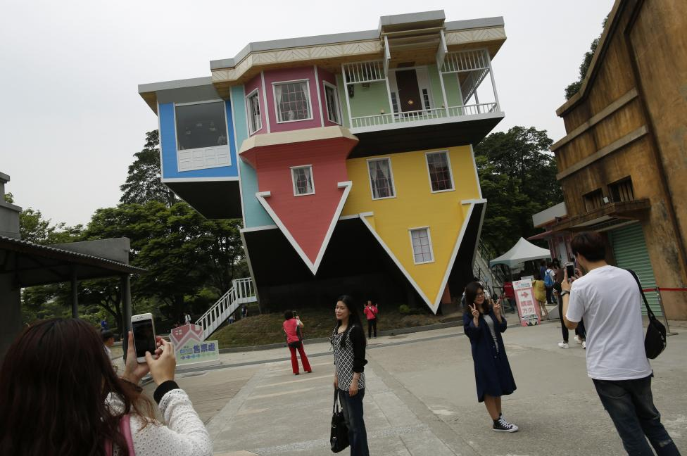 Visitors pose in front of a three story upside-down family sized house at the Huashan Creative Park in Taipei