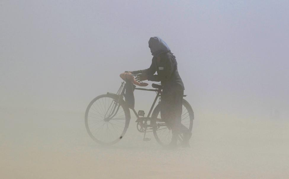 A man covers his face as he pushes a bicycle through a dust storm on the banks of the Ganga river in Allahabad