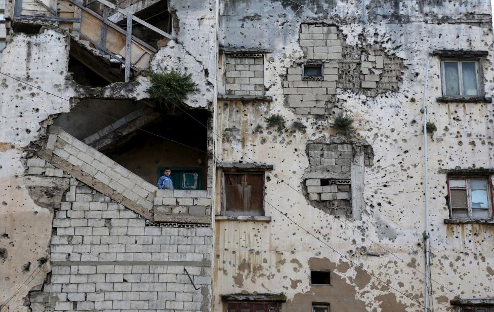 A boy stands on the staircase of a riddled building in Beirut