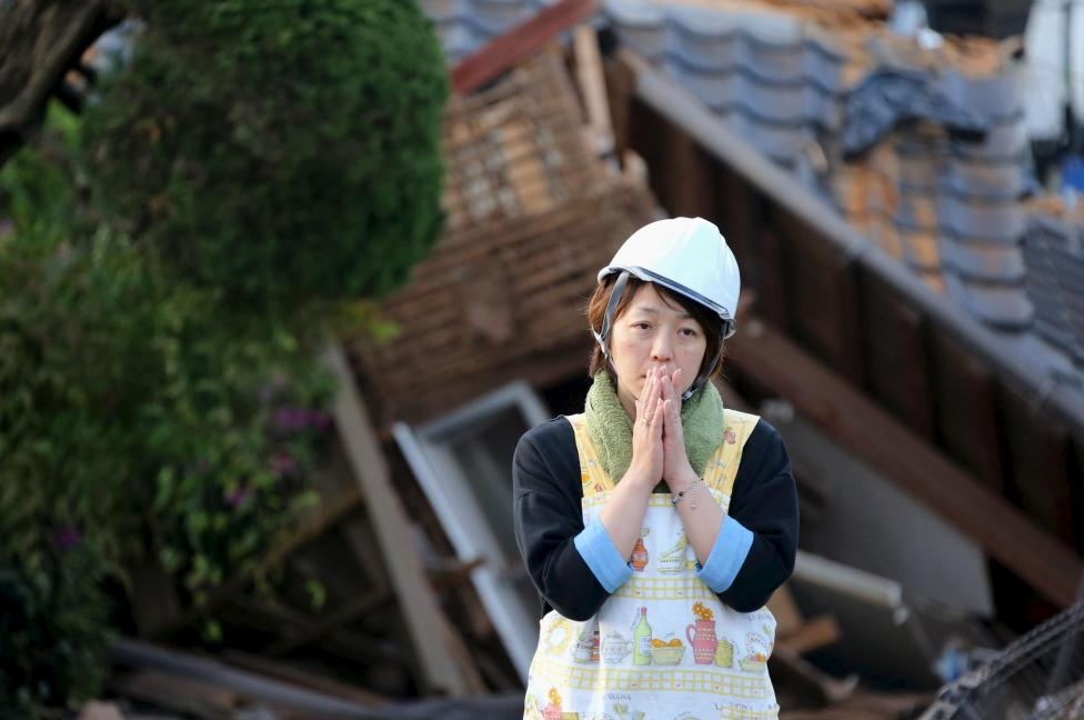 Woman reacts in front of collapsed house caused by an earthquake in Mashiki town