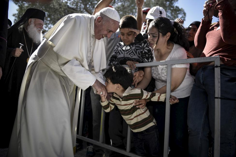 Handout photo of a boy shaking the hand of Pope Francis as he greets migrants and refugees at Moria refugee camp near the port of Mytilene, on the Greek island of Lesbos
