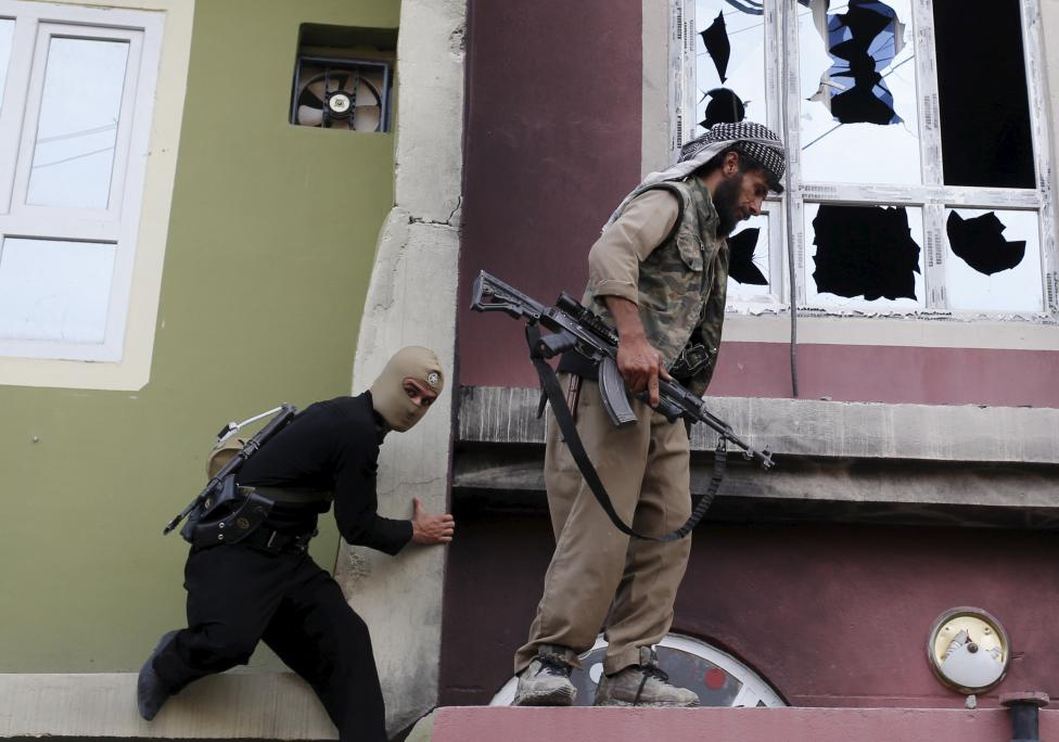Kurdish gunmen climb the house of a Shi'ite militiaman during clashes in Tuz Khurmato
