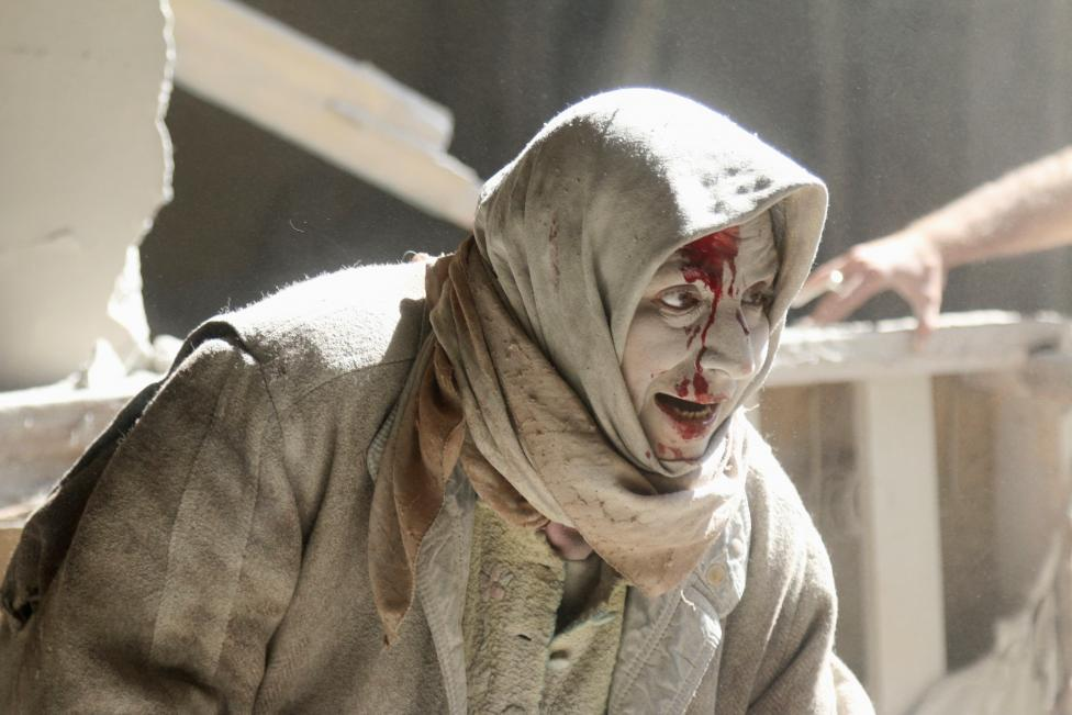 An injured woman reacts at a site hit by airstrikes in the rebel held area of Old Aleppo