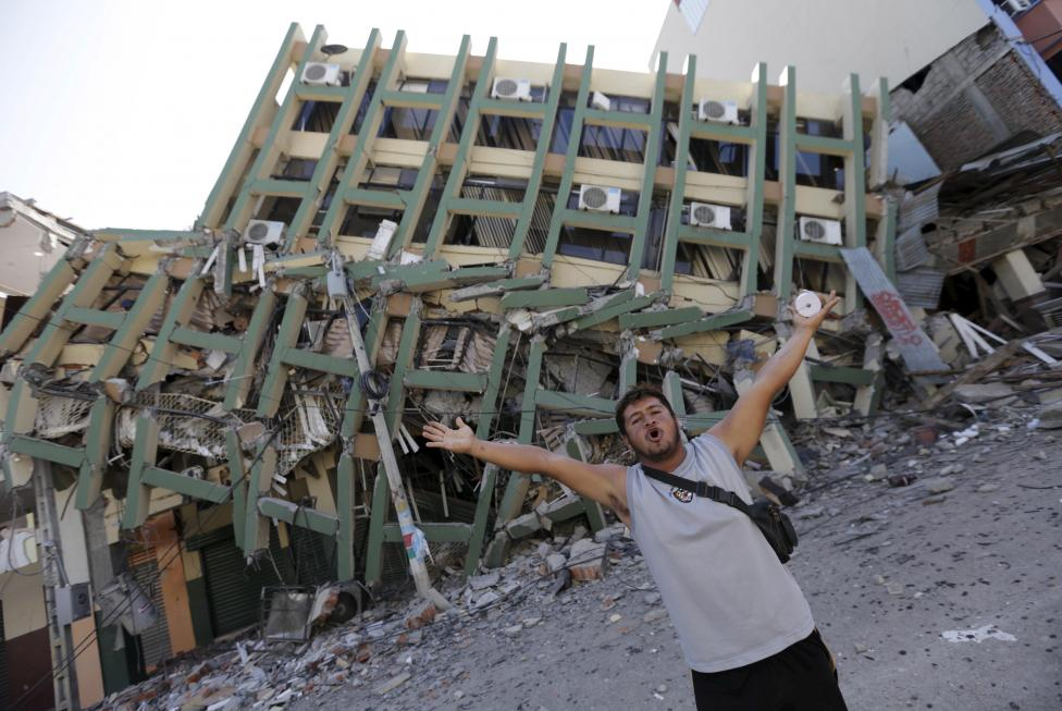 A resident gestures next to a collapsed building after an earthquake struck off the Pacific coast, in Portoviejo