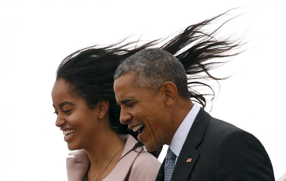 Malia Obama's hair flies into the air as a cold wind hits her and U.S. President Barack Obama while descending the steps of Air Force One upon their arrival at O'Hare Airport in Chicago