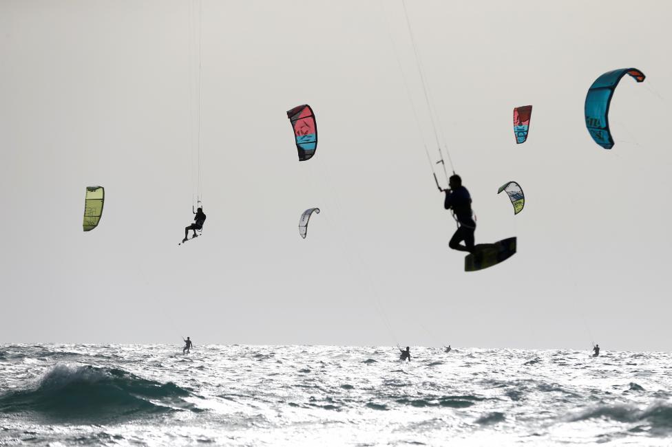 People kitesurf in the Mediterranean sea in Tel Aviv