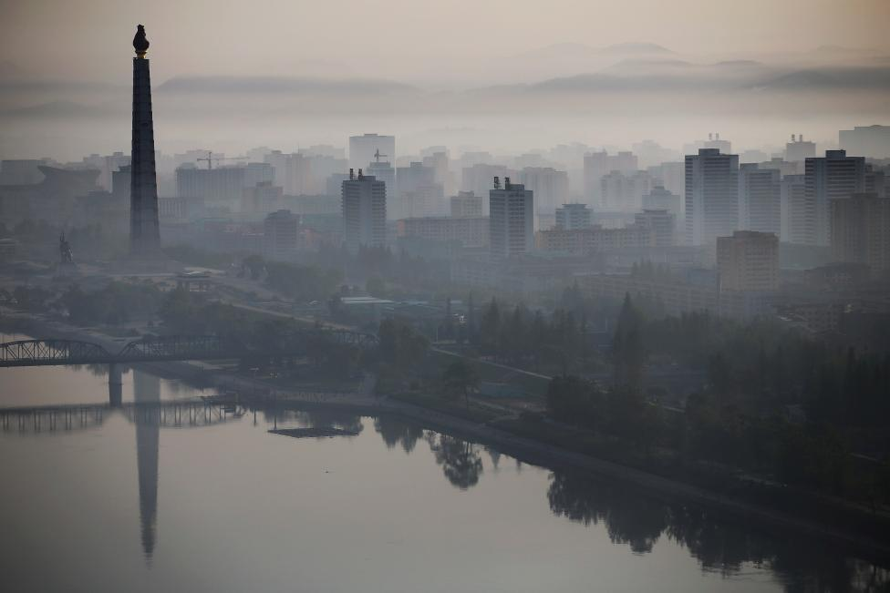 The 170-metre (558-feet) tall Juche Tower is reflected in Taedong River as morning fog blankets Pyongyang